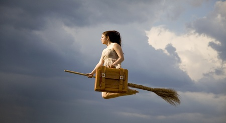 Young brunette witch on broom flying away