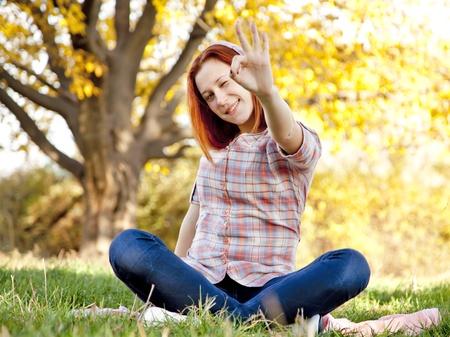 ok symbol: Ritratto di ragazza dai capelli rossi nel parco autunno. Show girl simbolo OK. Colpo esterno. Archivio Fotografico