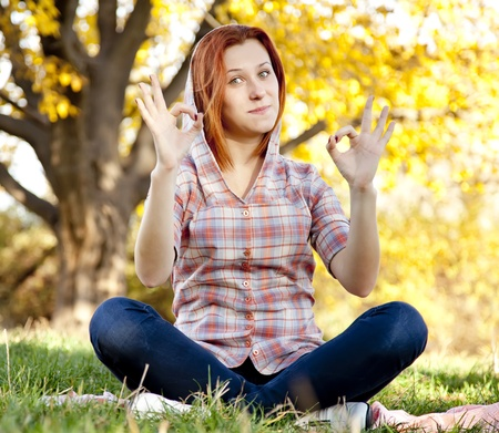 Portrait of red-haired girl in the autumn park. Girl show OK symbol. Outdoor shot. photo