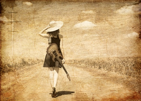 country: Rock meisje met gitaar op het platteland. Foto in oude beeld stijl.