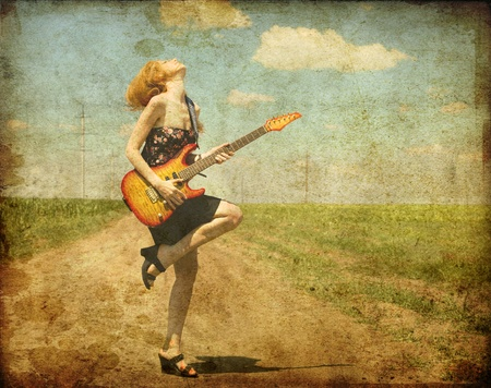classic woman: Rock girl with guitar at countryside. Photo in old color image style. Stock Photo