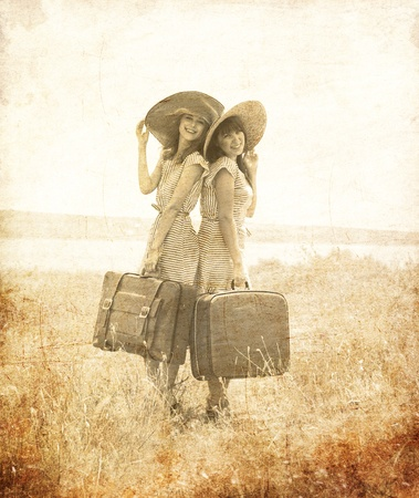 Two retro style girls with suitcases at countryside. Photo in old image style. Zdjęcie Seryjne
