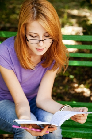 Redhead girl in glasses doing homework at the park. photo