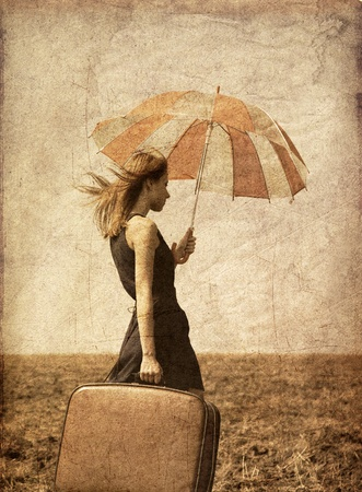 Redhead girl with umbrella at windy field. Stock Photo