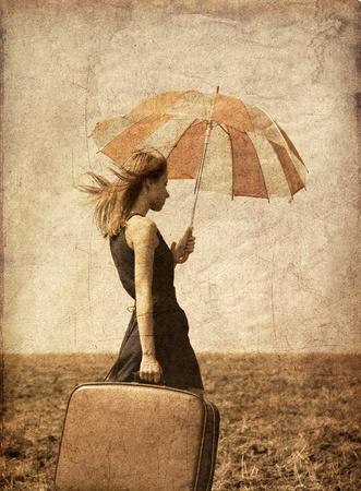 retro fashion: Redhead girl with umbrella at windy field. Stock Photo