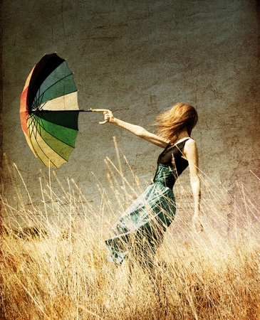 vintage woman: Redhead girl with umbrella at windy grass meadow.