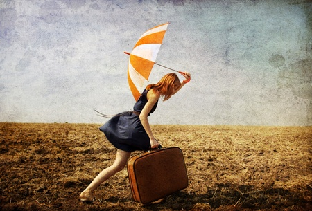 Lonely girl with suitcase and umbrella at countryside field. Photo in old image style.
