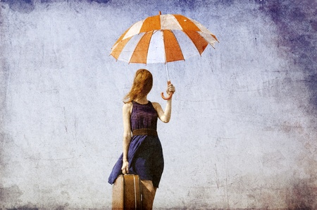 surreal: Lonely girl with suitcase and umbrella.  Photo in old image style
