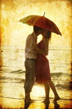 woman with umbrella: Couple kissing under umbrella at the beach in sunset. Photo in old image style. Stock Photo