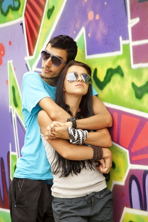 street fashion: Young couple near graffiti background.