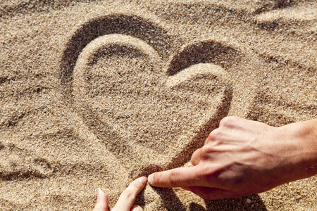 People drawing heart at sand. photo