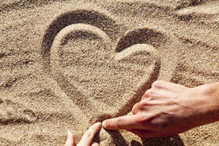 cuore in mano: Persone disegno cuore in sabbia. Archivio Fotografico
