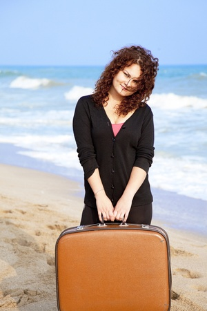 Redhead girl at outdoor with suitcase. photo
