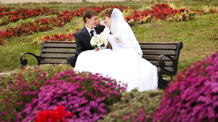 Young just married couple sitting close to each other on bench in park. photo