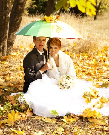 Couple sitting at the park with umbrella. photo
