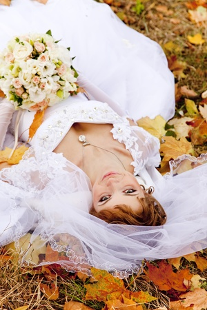 liying: Beautiful bride liying down in the park. Autumn time.
