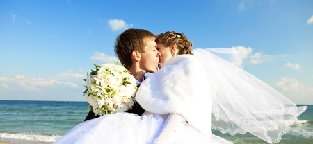 Newly married couple kissing on the beach. photo