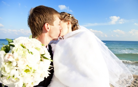 Newly married couple kissing on the beach. Stock Photo - 11011516