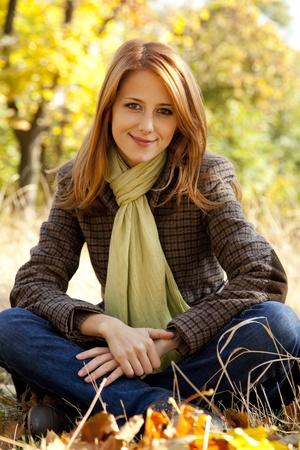 秋の公園で赤い髪の少女の肖像画。屋外のショット。