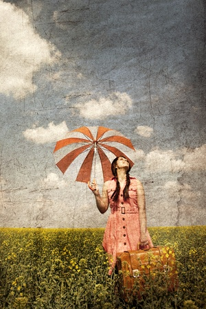 Brunette enchantress with umbrella and suitcase at spring rapeseed field. Photo in old image style. photo