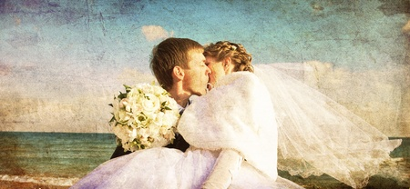Newly married couple kissing on the beach. Photo in old image color style. photo