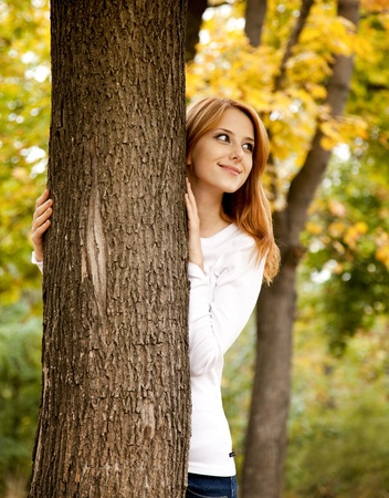 autumn hair: Portrait of red-haired girl in the autumn park. Outdoor shot.