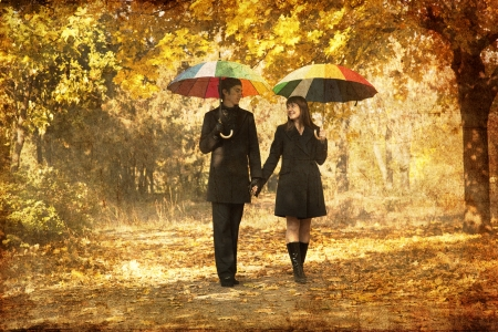 autumn city: Couple walking at alley in autumn park. Photo in old image style.
