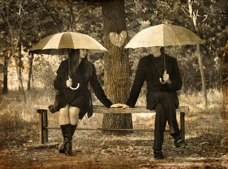 Two sitting at bench in rainy day. Photo in old image style. photo