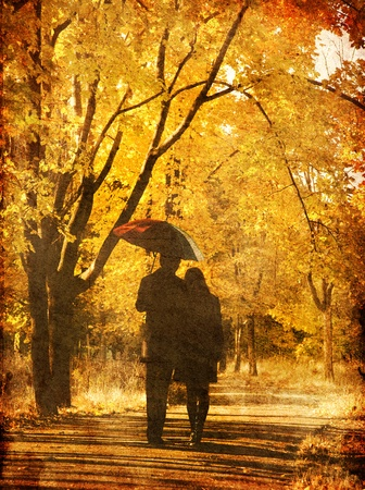 Couple walking at alley in autumn park. Photo in old image style. photo