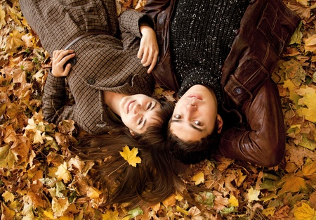 lying in leaves: Couple lying in the park in fall.