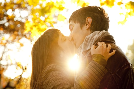 baiser amoureux: Couple s'embrassant dans le parc au coucher du soleil.