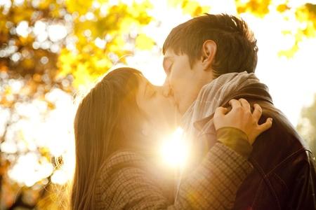 novios besandose: Pareja besándose en el parque al atardecer.