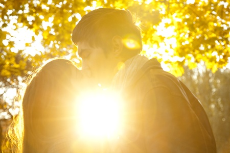 Couple kissing in the park at sunset. photo