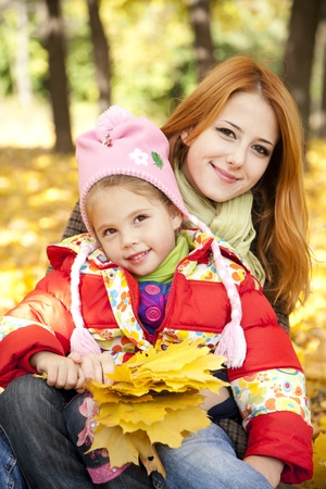 Mother and daughter in autumn yellow park. photo