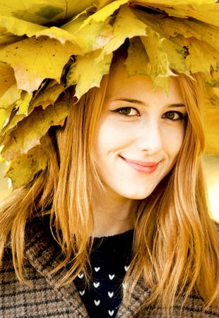 Smiling happy girl in autumn leaves. Outdoor. photo