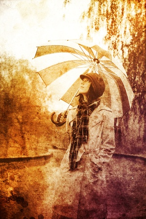 Girl in cloak and scarf with umbrella at park in rainy day. Photo in multicolor vintage style. photo