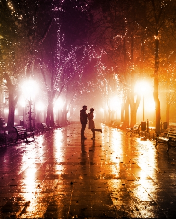 Couple walking at alley in night lights. Photo in vintage multicolor style. photo