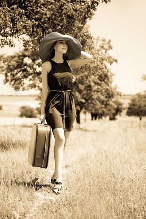 Lonely girl with suitcase at countryside. photo