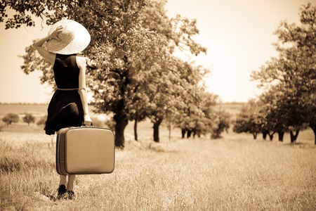 Lonely girl with suitcase at countryside. Stock Photo