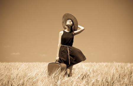 mujer con maleta: Chica con la maleta en el campo de trigo de verano. Foto en el viejo estilo de imagen en color amarillo. Foto de archivo