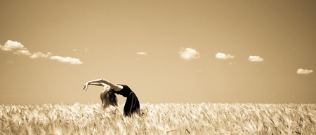 Girl at summer wheat field. Photo in old yellow color image style. photo