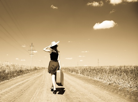 Lonely girl with suitcase at country road. Photo in old yellow color image style. photo