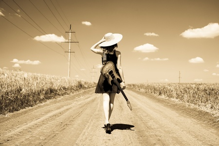 country music: Rock girl with guitar at countryside. Photo in old yellow color image style.
