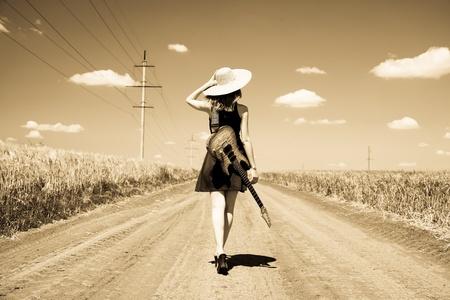 gitara: Rock girl z gitarą na wsi. Zdjęcie w starym stylu żółty kolorowy obraz.