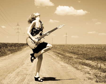 Rock girl with guitar at countryside. Photo in old yellow color image style.