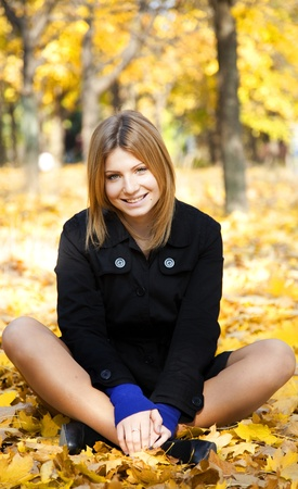 Smiling happy girl in autumn park. photo