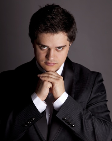 Style young brunette man with black tuxedo. photo