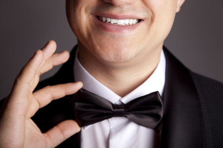A close-up shot of a man straightening his tux. photo