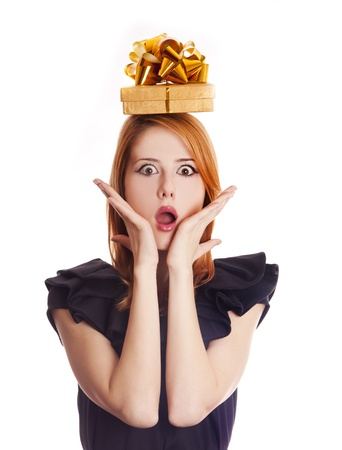 Red-haired girl in dress with present box over head. photo