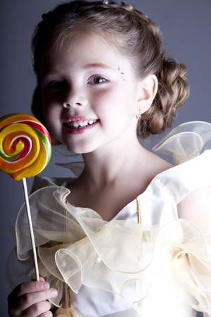 Beautiful pretty little girl with candy Stock Photo - 11410438